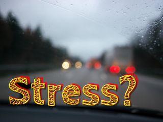 """Verschwommener Blick durch eine Auto-Frontscheibe und davor der Text """"Stress?"""""""