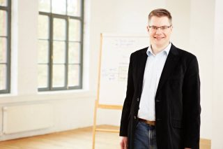 Bernd Sauer vor einer Flipchart im Seminarraum