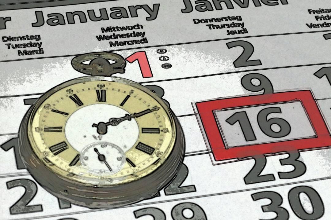 Eine Taschenuhr liegt auf einem Kalender